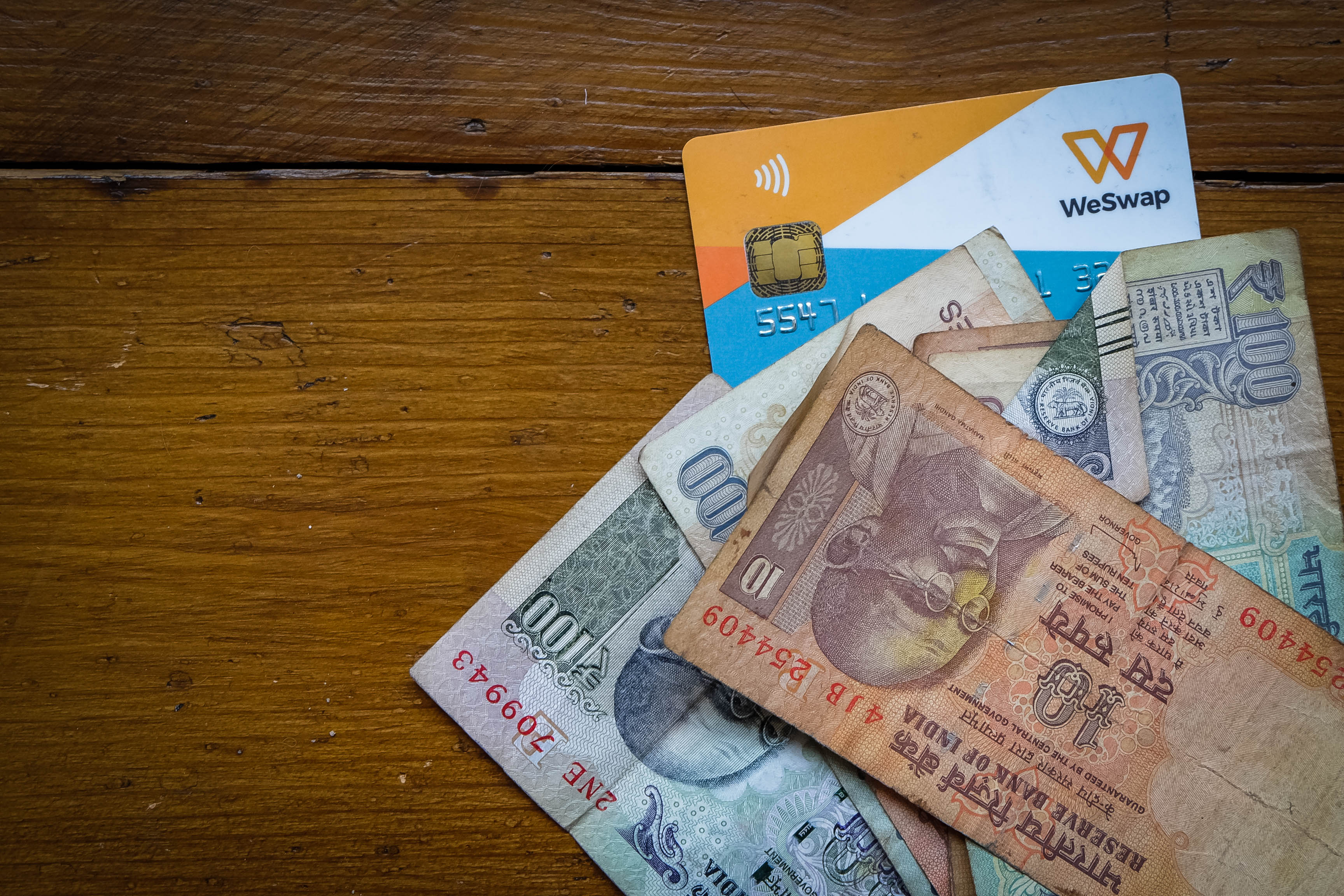 WeSwap currency card on a table with Indian Rupee notes