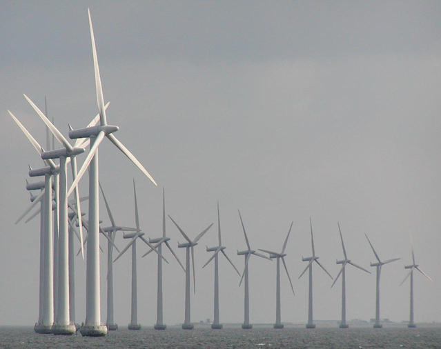 Line of windmills in a wind farm in the sea